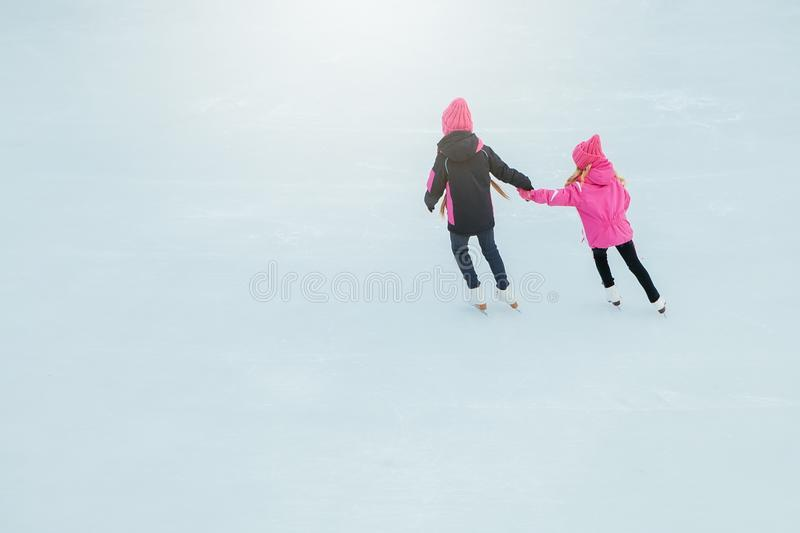 Two Little smiling girls skating on ice in pink wear and hand made scarfs. Outdoor. Winter royalty free stock image