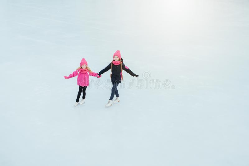 Two Little smiling girls skating on ice in pink wear and hand made scarfs. Outdoor. Winter royalty free stock photo