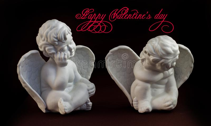 Two little stone angels sitting opposite each other royalty free stock photos