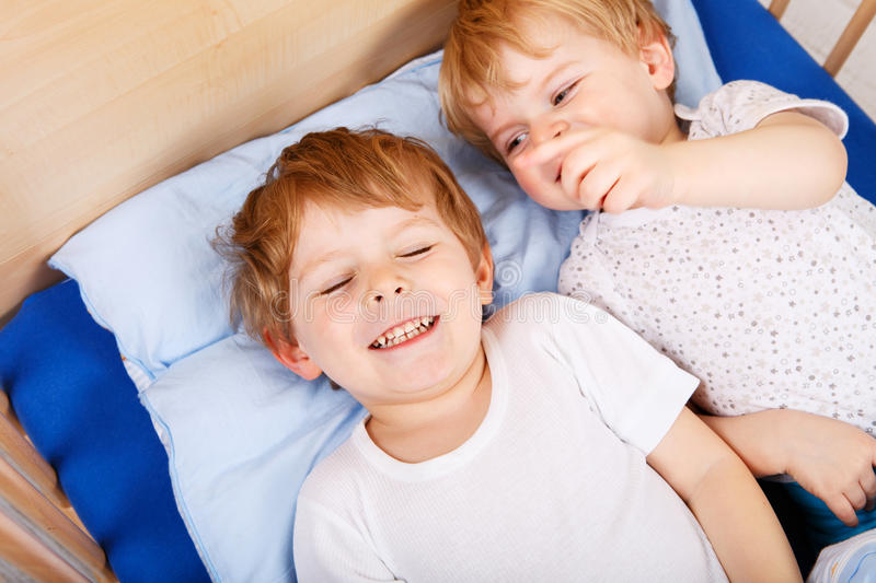 Download Two Little Toddler Boys Having Fun In Bed Stock Photo
