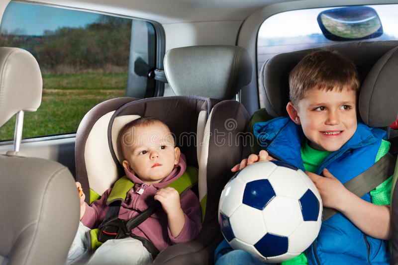 Two little travelers sitting in child safety seats. Two happy little travelers, age-diverse brothers, playing ball, sitting in a child safety seats stock images