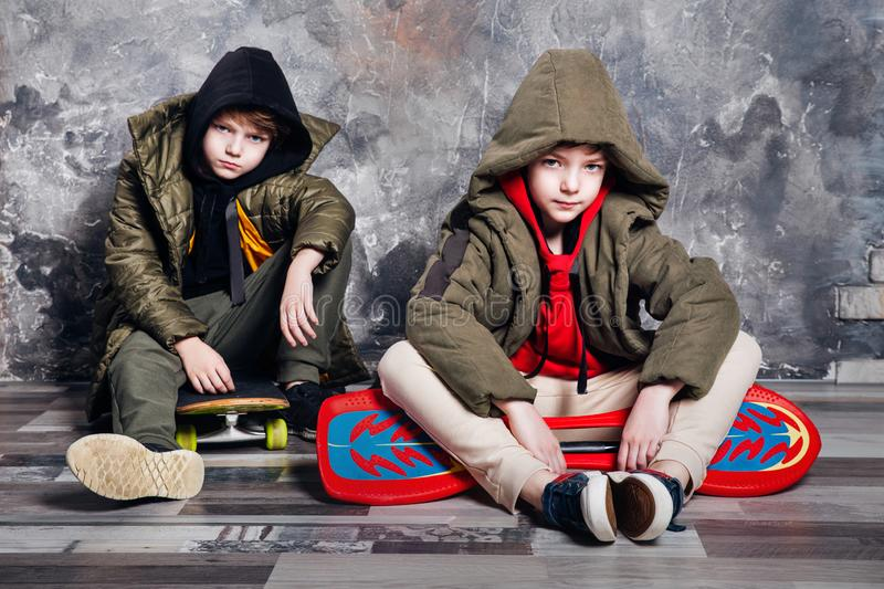 Two little twin boys in casual clothes sitting on skateboard in studio. Teen and kids fashion concept. Two little twin boys in casual clothes sitting on royalty free stock images