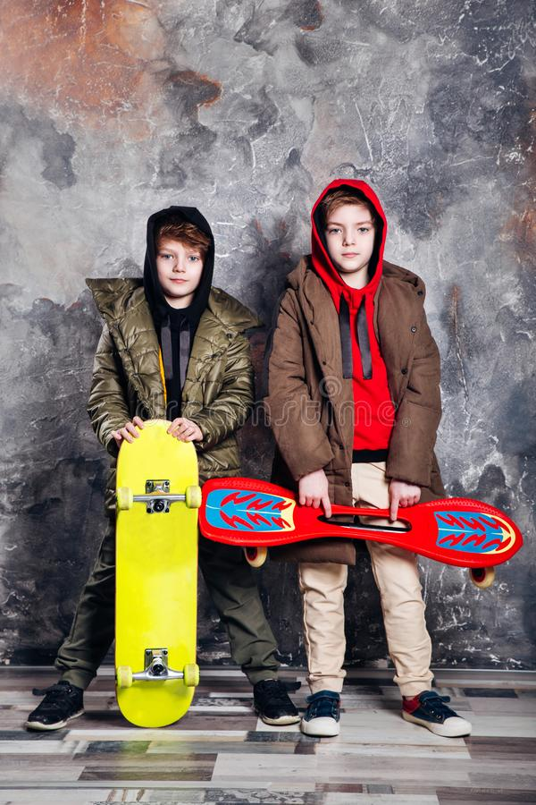 Two little twin boys in casual clothes with skateboards in studio. Teen and kids fashion concept. stock photo