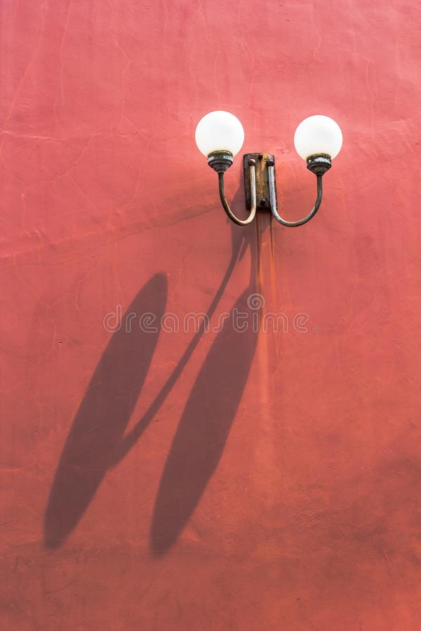 Two llight on red wall. With shadow stock photography