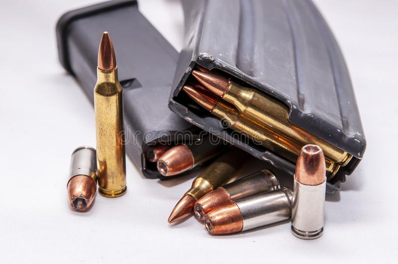 Two loaded magazines, one for a 223 caliber rifle and the other for a 9mm pistol along with additional bullets for each. On a white background stock photography