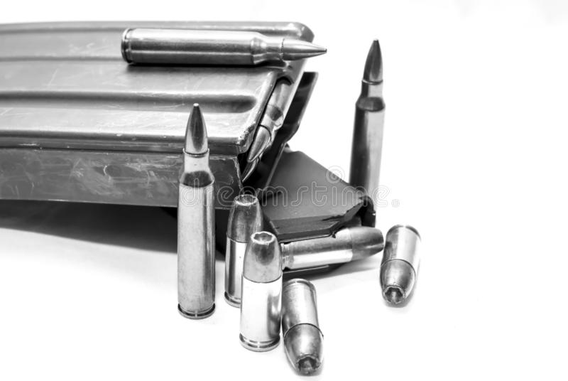 Two loaded magazines, one for a 223 caliber rifle and the other for a 9mm pistol along with additional bullets for each. On a white background shot in black and royalty free stock image