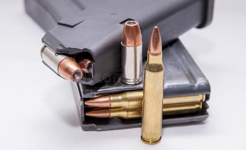 Two loaded magazines, one for a 9mm pistol and the other for a 223 caliber rifle. On a white background stock photo