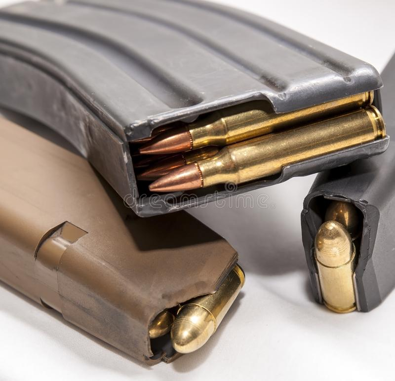 Two loaded 9mm pistol magazines with a loaded 223 caliber magazine. On a white background royalty free stock photos