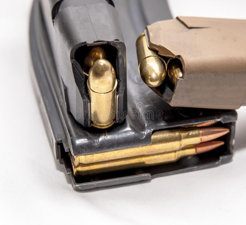 Two loaded 9mm pistol magazines with a loaded 223 caliber magazine. On a white background royalty free stock images