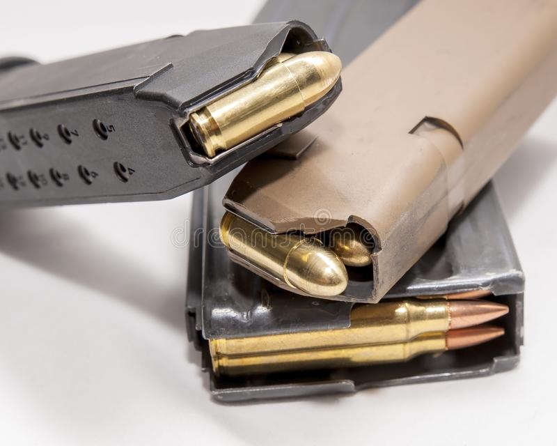 Two loaded 9mm pistol magazines with a loaded 223 caliber magazine. On a white background stock photo