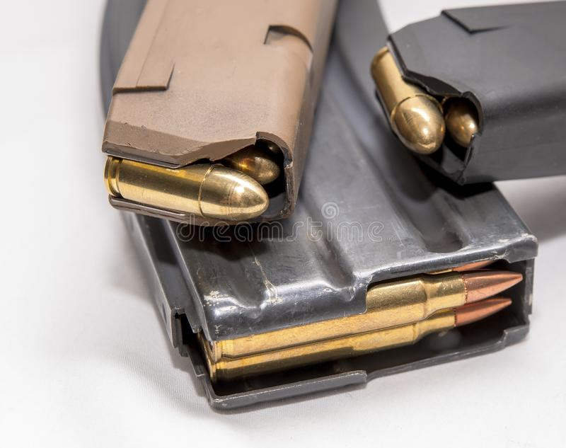 Two loaded 9mm pistol magazines with a loaded 223 caliber magazine. On a white background stock image