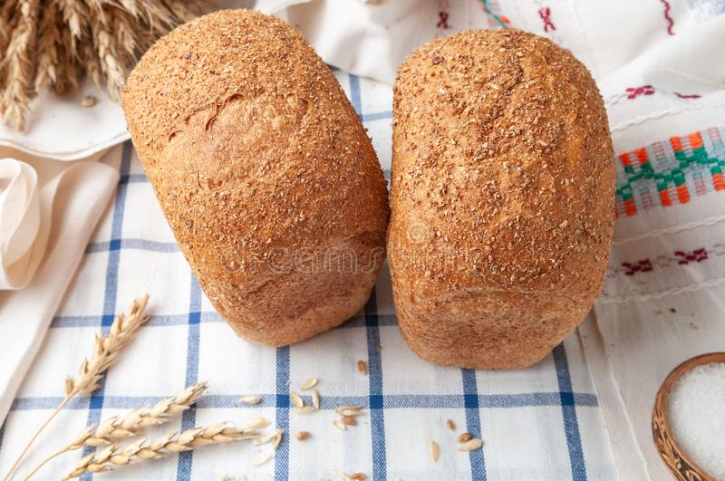 Two loaves of bran bread. On a white blue striped tablecloth. On the tablecloth ears of wheat and grain. View from above. Country stock images