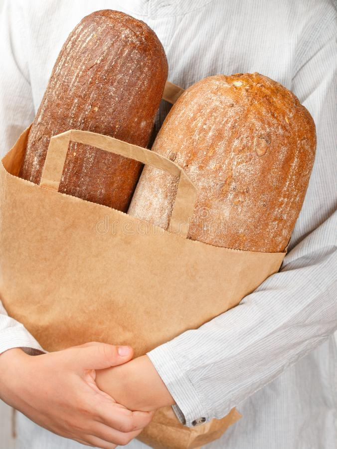 Two loaves of bread in a paper bag in his hands. Rye and wheat loaf. Selective focus royalty free stock images