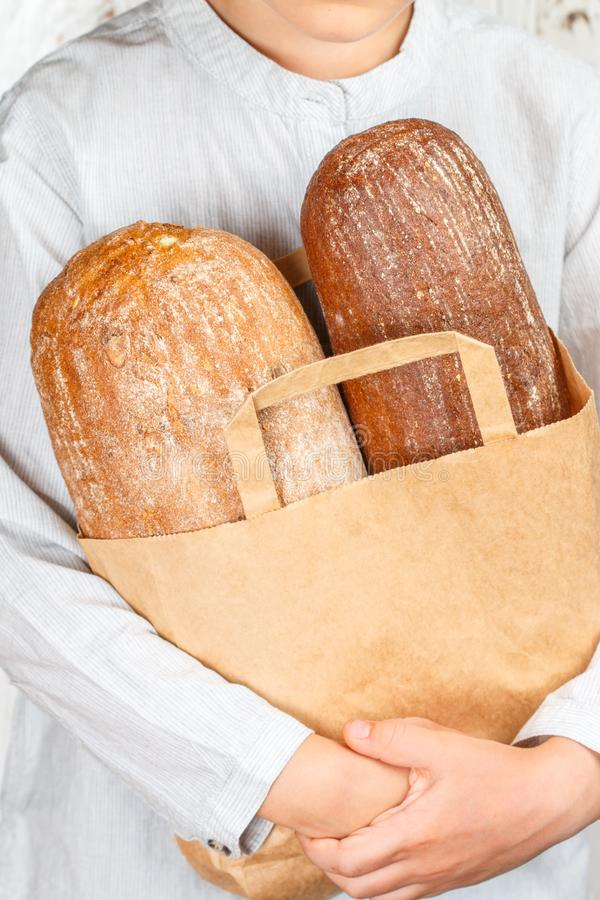 Two loaves of bread in a paper bag in his hands. Rye and wheat loaf. Selective focus stock images