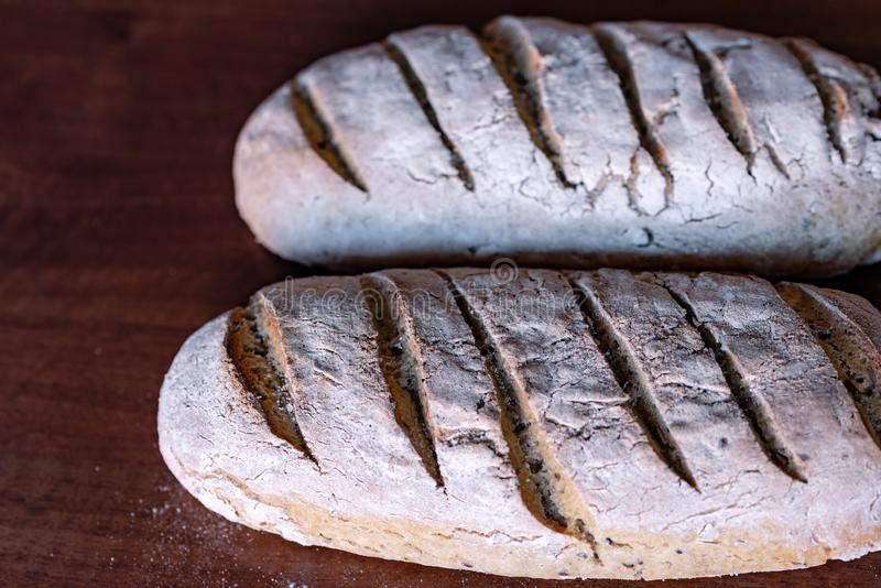 Two loaves of bread with sesame seeds, flax and pumpkin, leavened with sourdough royalty free stock photography