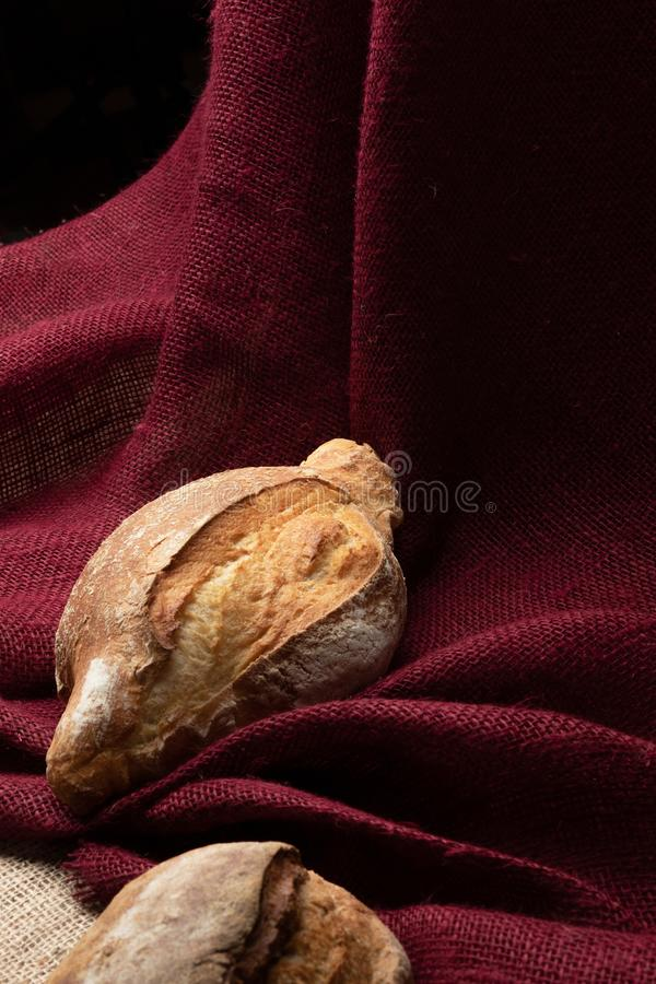 Two loaves of bread on the table against the background of colorful burlap,closeup royalty free stock image