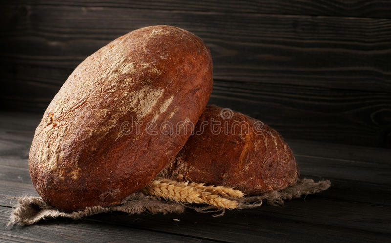 Two loaves of fresh rye bread with ears of wheat stock photo