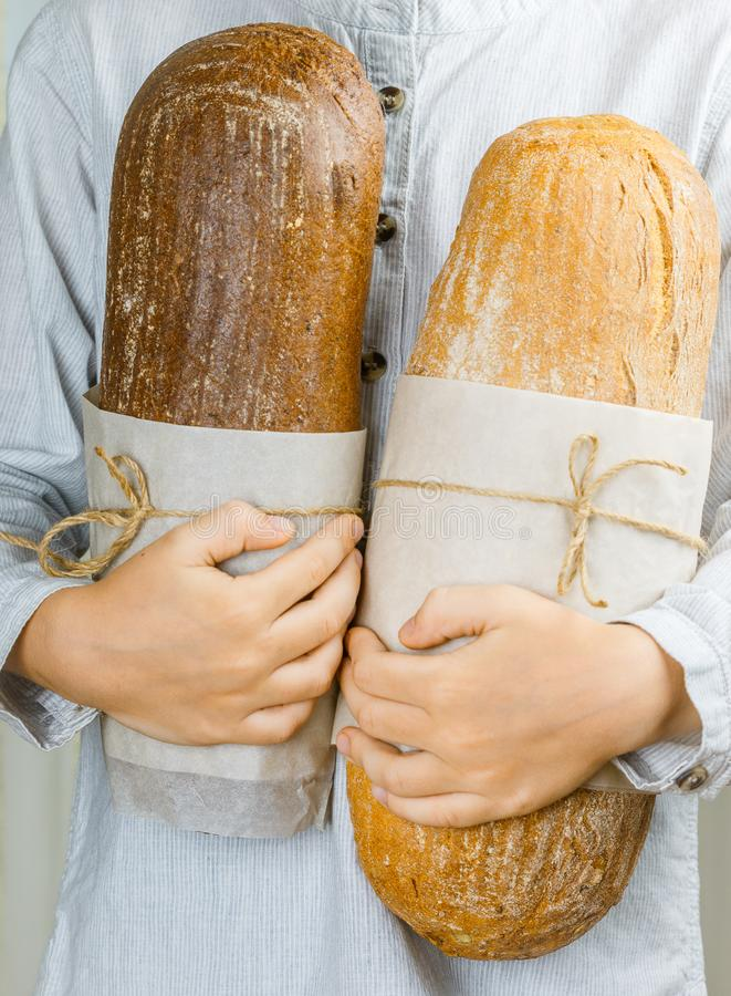 Two loaves of fresh wheat and rye bread in children`s hands. Selective focus stock photo