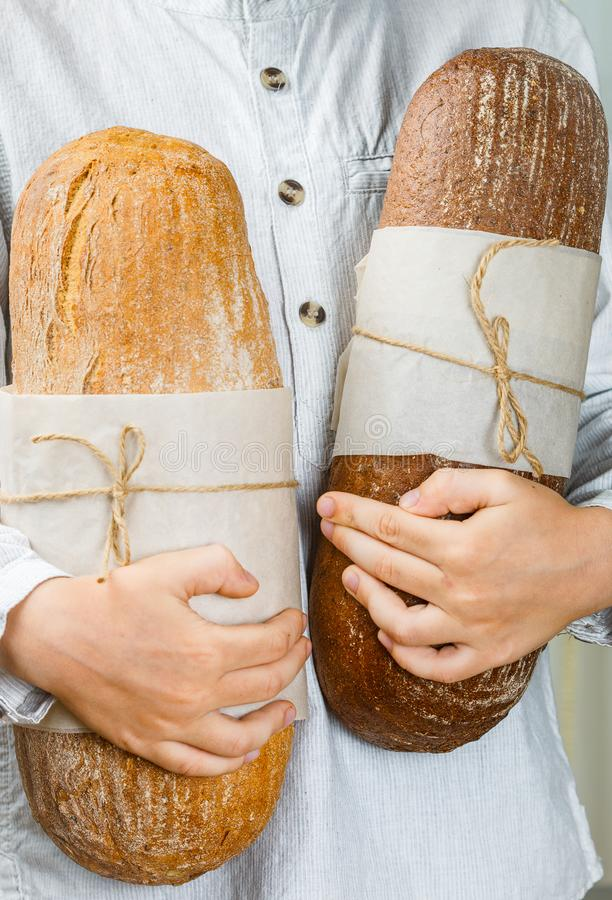 Two loaves of fresh wheat and rye bread in children`s hands royalty free stock image