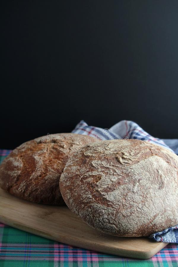 Two loaves of rye brown bread. On the table with a napkin beneath stock photo
