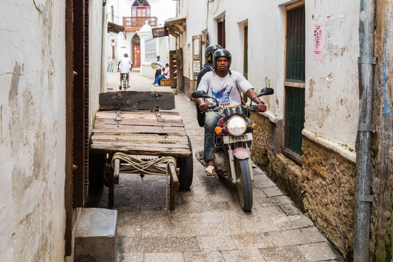 Two local men driving a motorcycle through narrow streets of Stone Town, old colonial center of Zanzibar City, Unguja, Tanzania. royalty free stock image