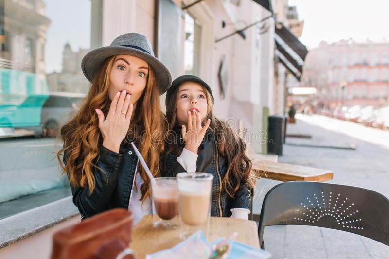 Two long-haired curly sisters looking with love each other, enjoying sunny morning in outdoor cafe. Positive little girl royalty free stock photos