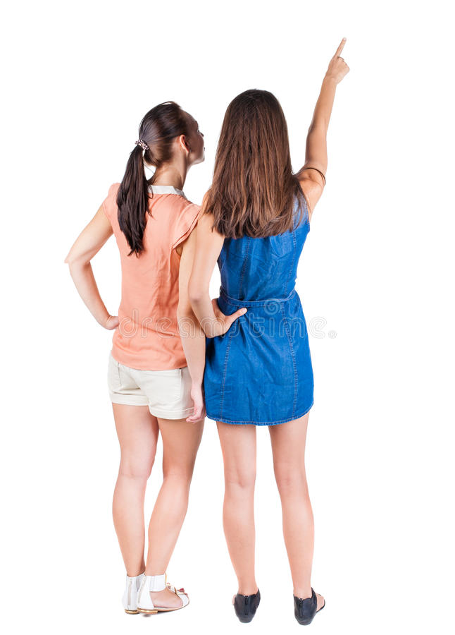 Two long haired friendly women pointing . royalty free stock photography