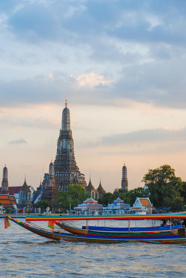 Two Long Tail boats at Wat Arun. Wat Arun is among the best known of Thailand's landmarks and the first light of the morning reflects off the surface of the royalty free stock photography