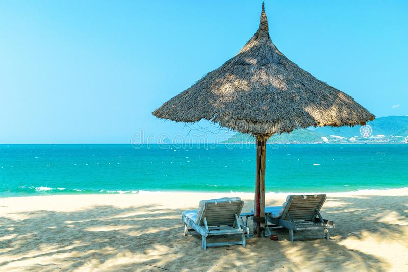 Two loungers under strawy parasol on sandy beach stock photo
