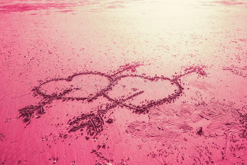 Pink two love heart sign with cupid arrow hand draw on the beach stock photography