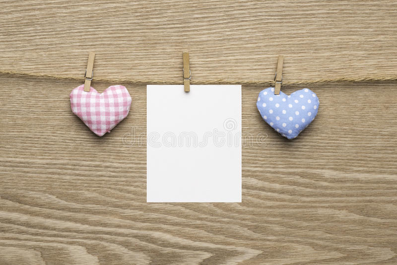 Two love hearts with blank instant photos over wooden background stock images