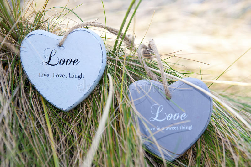Two love hearts on grassy dunes. Two blue wooden love heart in dunes on an Irish beach royalty free stock photography