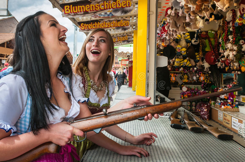 Two lovely girls playing shooting games and having. Two attractive and beautiful girls playing shooting games, having fun at German funfair Oktoberfest. Wearing stock image