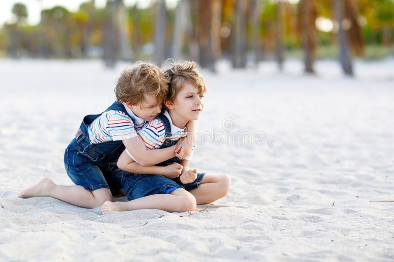 Two lovely little brothers sitting on sand on tropical beach, happy best friends, kids boys playing, friendship concept stock photo