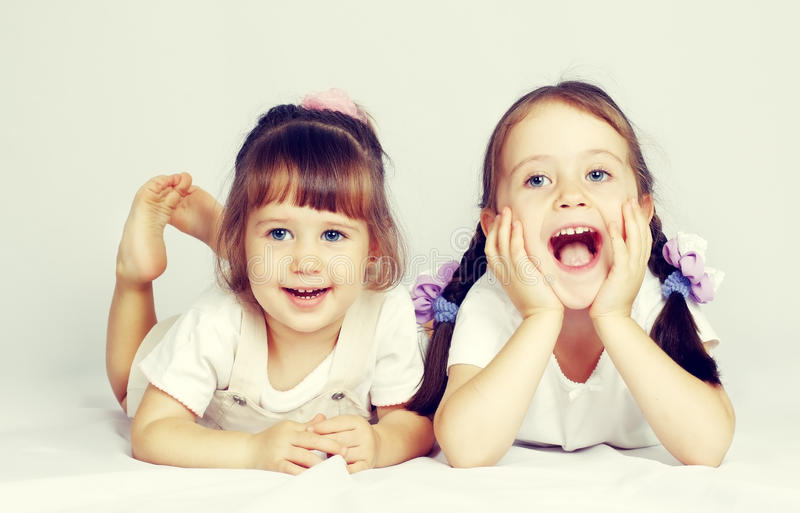 Two lovely little girls playing on the floor. Islated royalty free stock photos