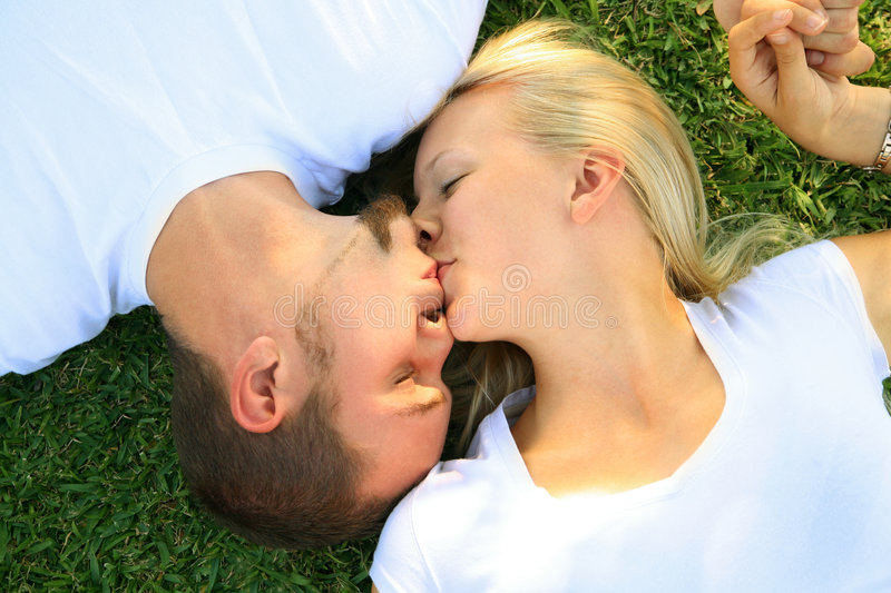 Two Lovely Man Woman Caucasian Kissing On Grass royalty free stock images