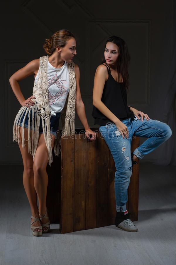 Two lovely women posing in a studio stock photography