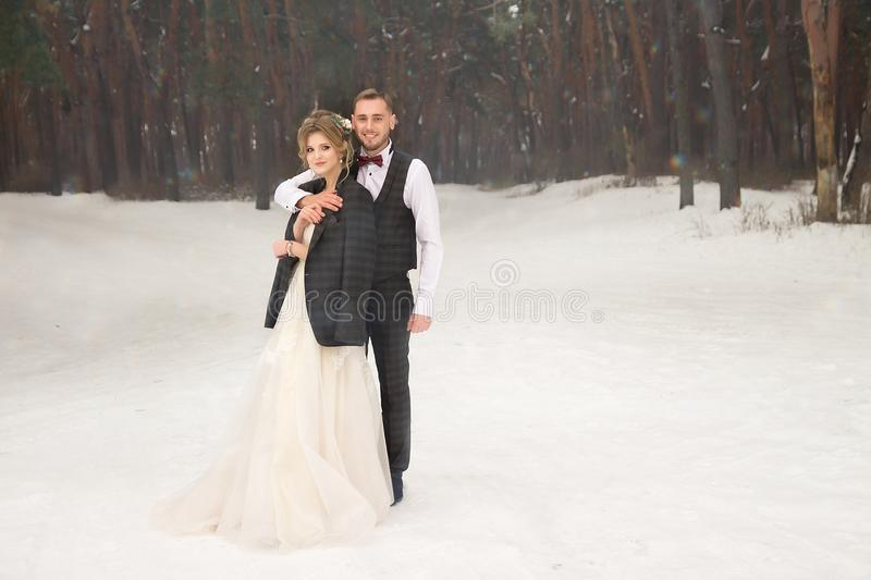 Two lovers in the forest, a happy couple, hugging, craving. smile, bride and groom. wedding in winter. suit and wedding dress. stock photography
