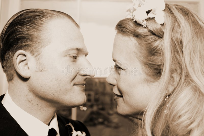 Two Lovers Gaze. Two lovers, dressed in classy attire, exchange a meaningful gaze filled with love. Set in beautiful sepia stock photo