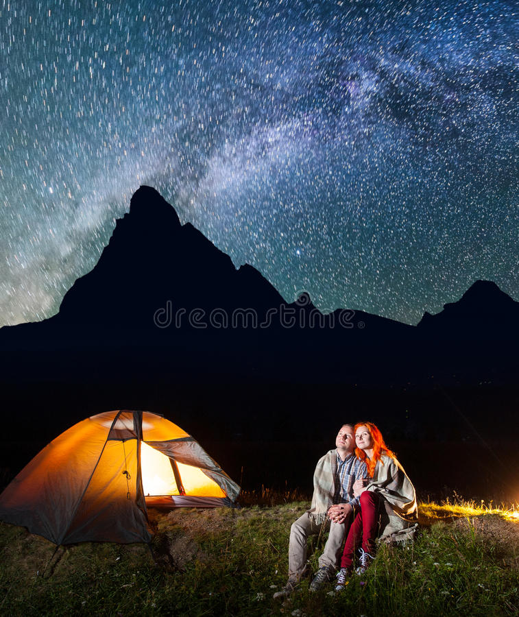 Two lovers hikers sitting together near campfire and shines camp at night under stars and looking to the starry sky. Two lovers hikers covered with a plaid stock photos