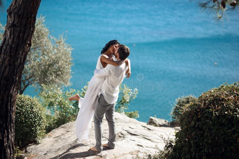 Two lovers kiss and embrace a coast behind the Mediterranean Sea during summer vacation time for couple in Greece. royalty free stock images