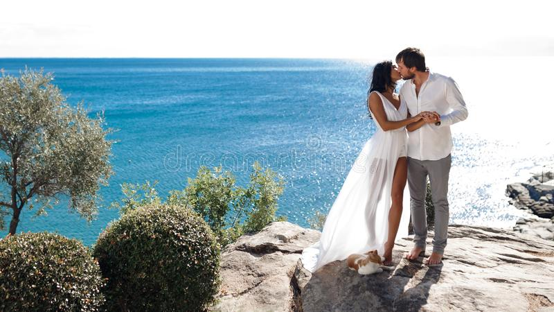 Two lovers kiss and embrace on a coast behind mediterranean seascape, summer time, just married. stock image