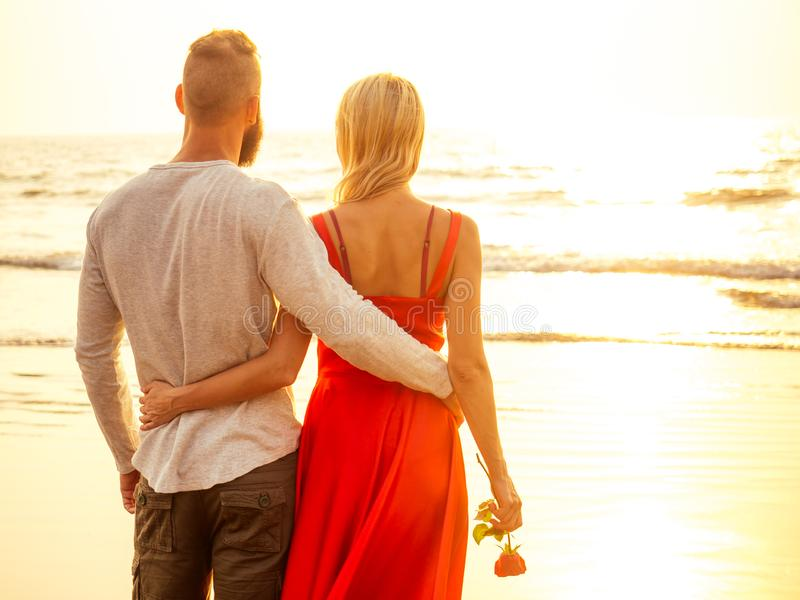 Two lovers people at sunset by the sea romance and tenderness feelings first love date.man and woman blonde in a dress stock photo
