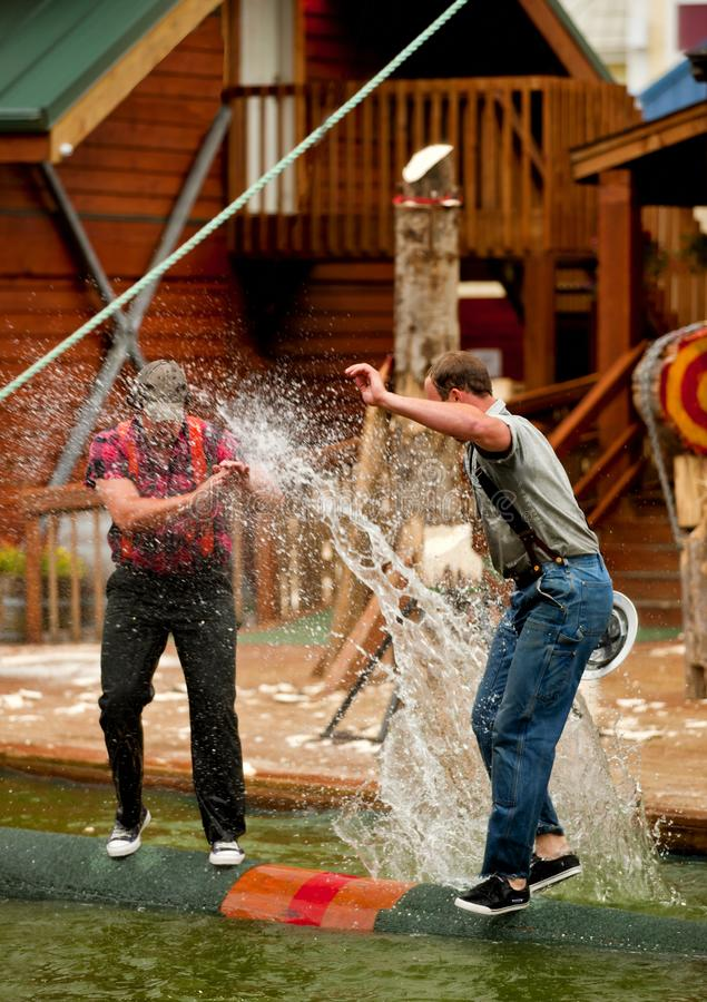 TWO LUMBERJACKS IN A LOG ROLLING COMPETITION OVER WATER royalty free stock images