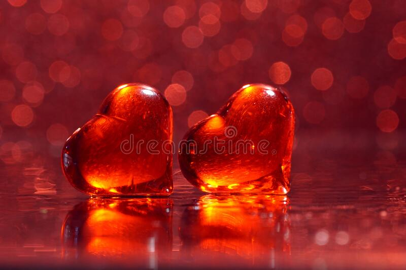 Valentine Romaance -Two luminous red hearts on a mirror bokeh background stock photography