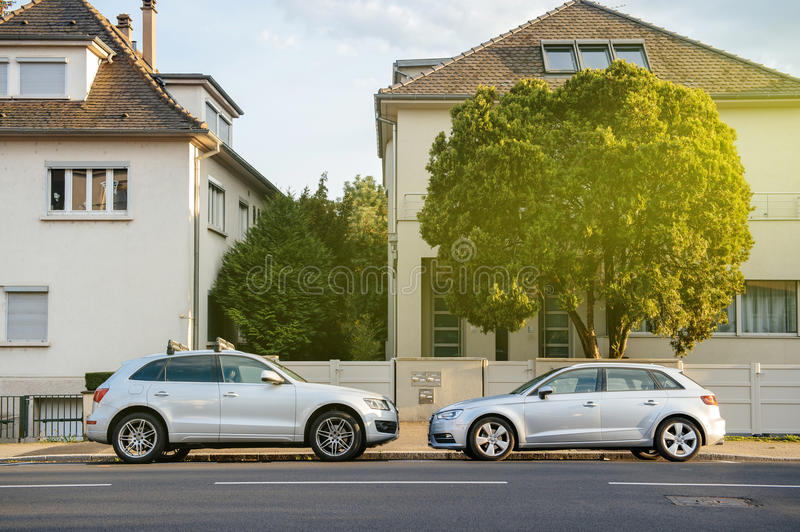 Two luxury AUDi cars parked in front of the large houses royalty free stock images