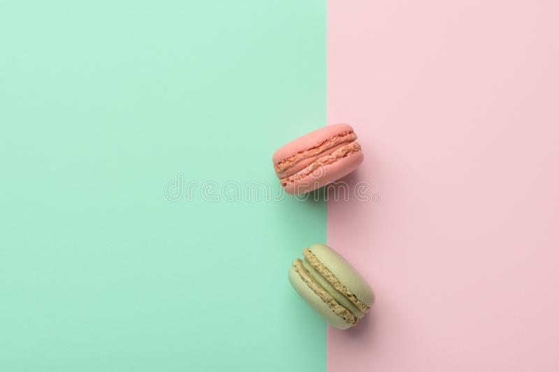 Two macarons strawberry and pistachio flavor on duotone pastel green chartreuse pink background. French pastry confectionery royalty free stock image