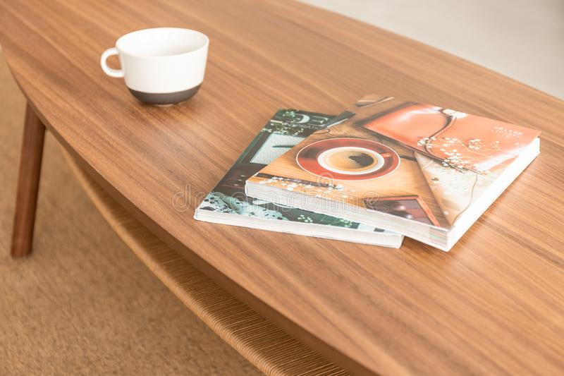 Magazines and coffee mug on the table, real photo. Two magazines and empty coffee mug on the wooden table, real photo stock photo