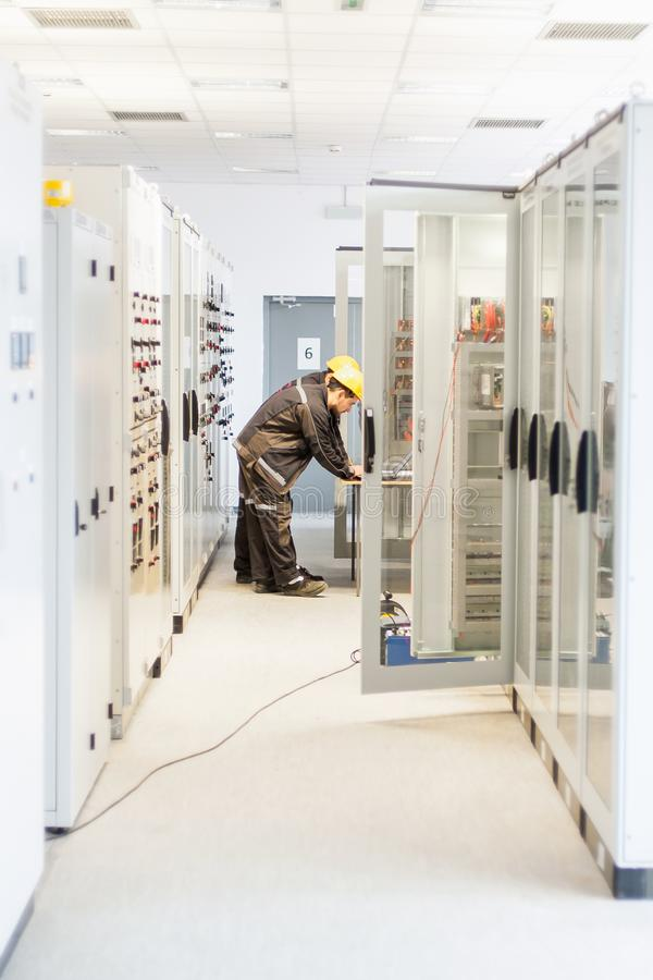 Two maintenance engineer work on relay protection system. Bay control unit. Medium voltage switchgear royalty free stock images