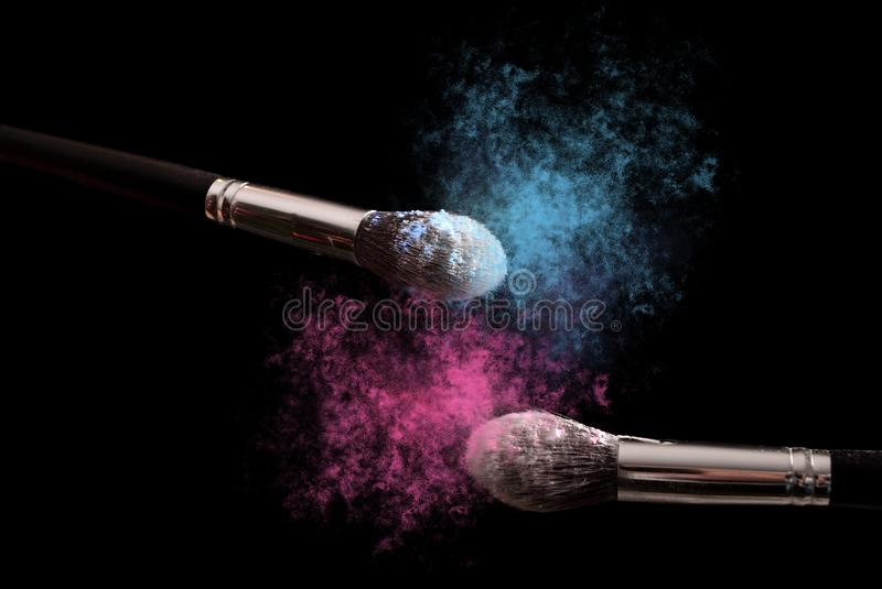 Two make up brushes with powder explosion dust in blue and purple color royalty free stock image